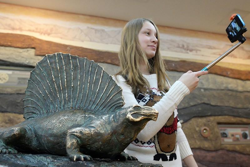 Посетительница делает селфи на фоне экспоната музея