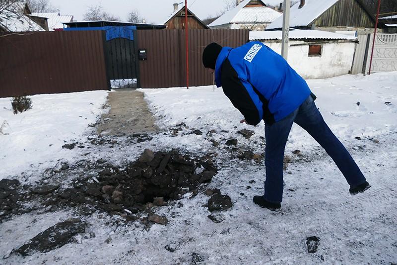Сотрудник ОБСЕ осматривает воронку от 122-мм артиллерийского снаряда