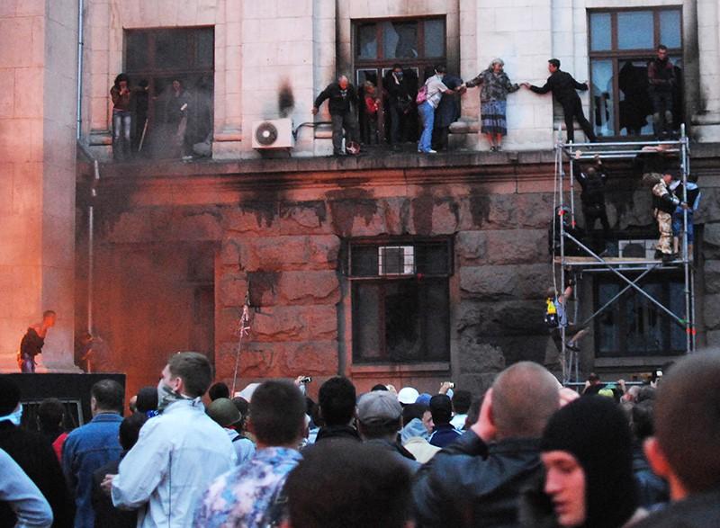 Люди выбираются на карниз здания во время пожара в Доме профсоюзов в Одессе