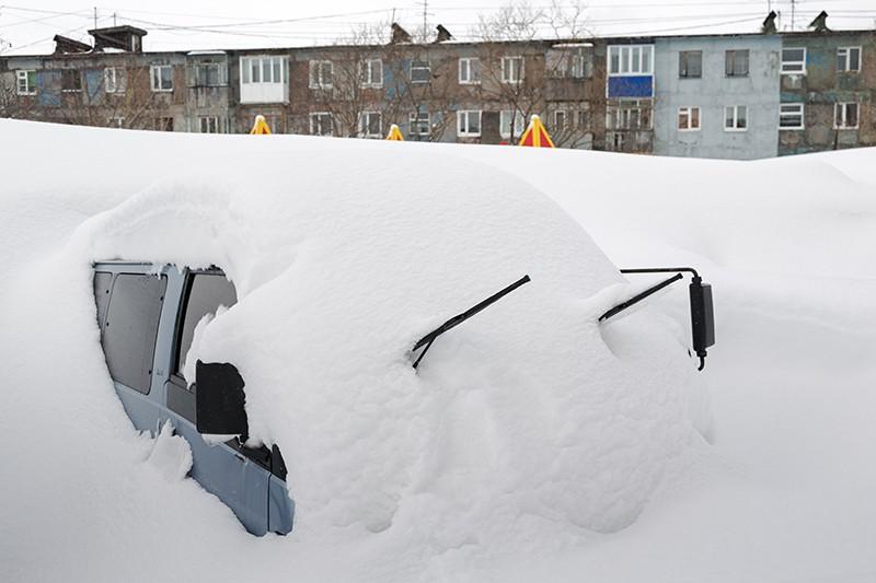 Занесенный снегом автомобиль после мощного цилона