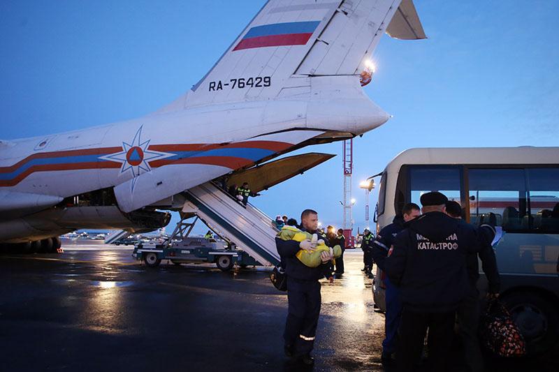 Сотрудник МЧС России переносит тяжелобольного ребенка, прибывшего из Донбасса