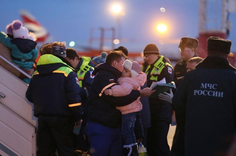 Сотрудник МЧС России переносит тяжелобольного ребенка, прибывшего из Донбасса в автомобиль скорой помощи