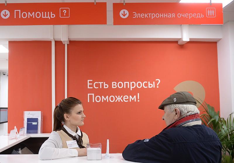 Сотрудница и посетитель центра государственных услуг в Москве
