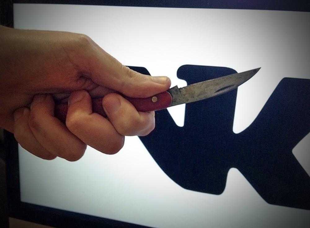 Нож в руке на фоне логотипа соцсети ВКонтакте