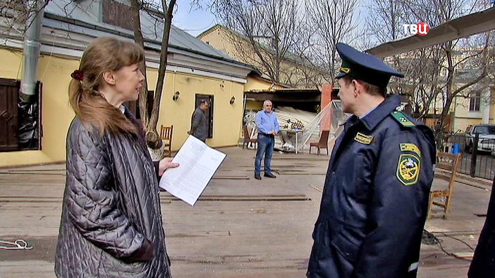 Инспекторы по недвижимости проверяют уличное кафе