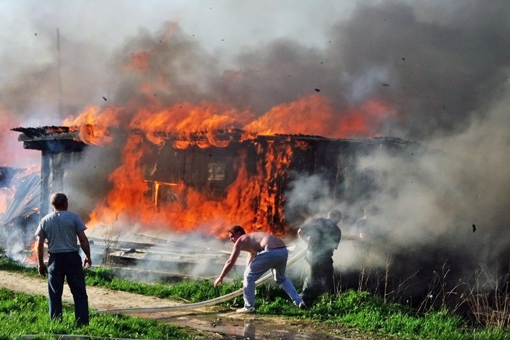 Люди тушат горящий дом