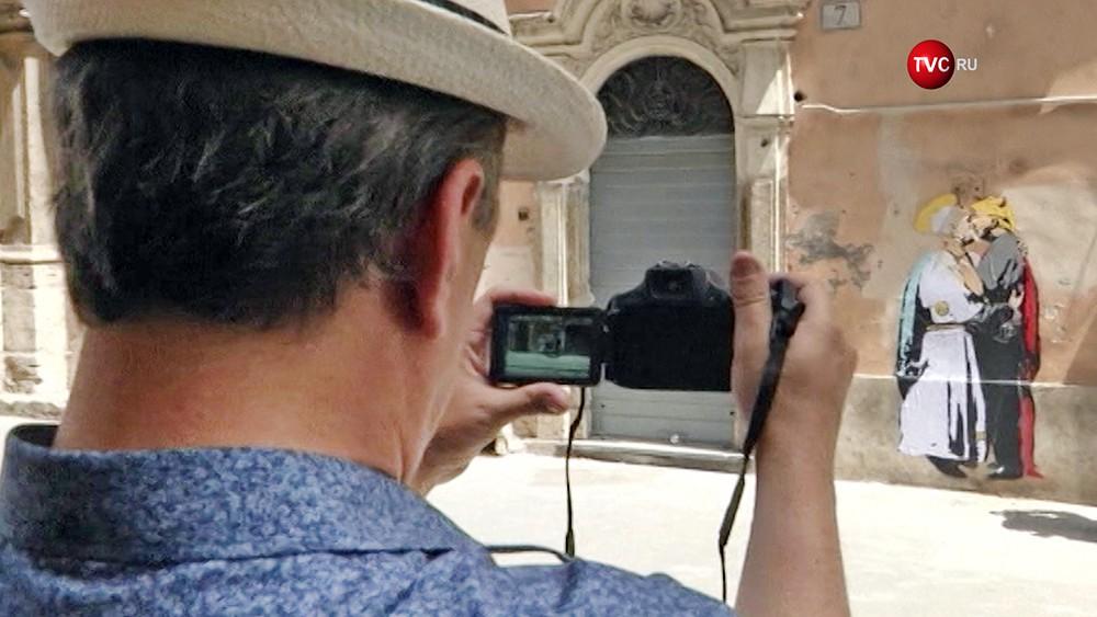 Люди фотографируют граффити целующихся Франциска и Трампа