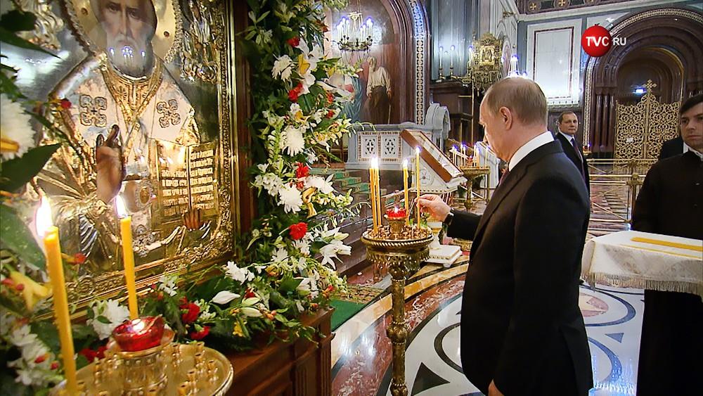 Владимир Путин ставит свечу к иконе святителя Николая Чудотворца в Храме Христа Спасителя