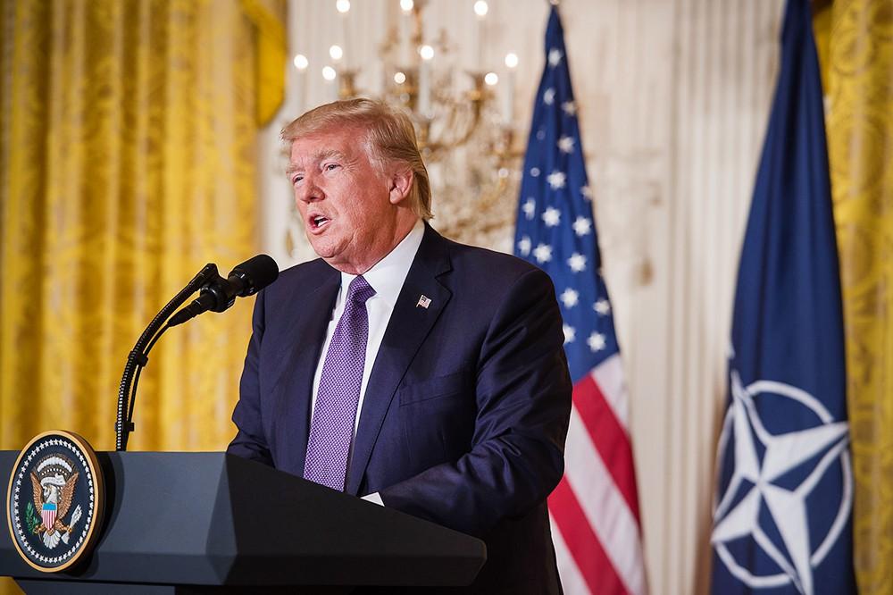 Дональд Трамп на фоне флагов США и НАТО