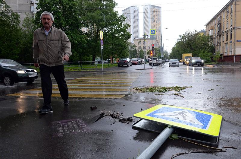 Поваленный ураганом дорожный знак на одной из улиц в Москве