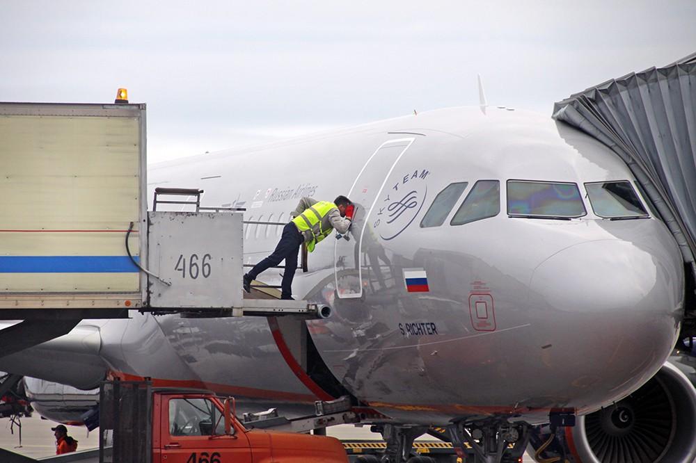 Служащие аэропорта у самолета