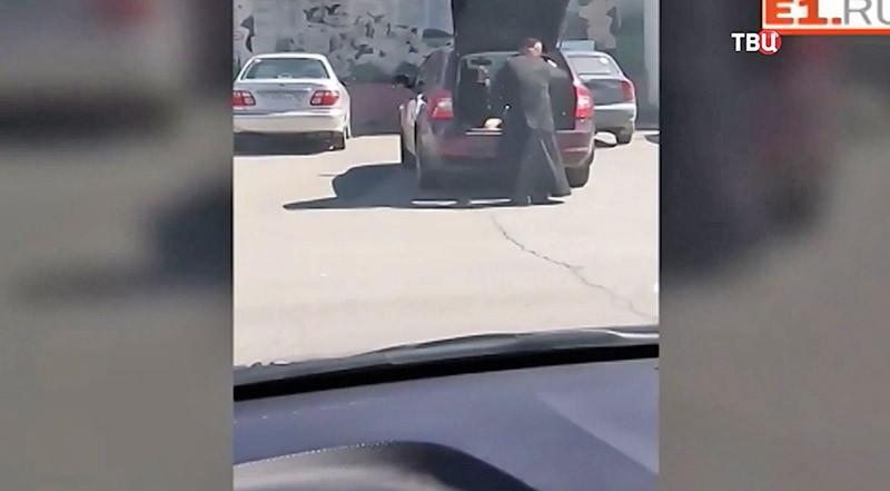 Cвященник сажает ребенка в багажнике
