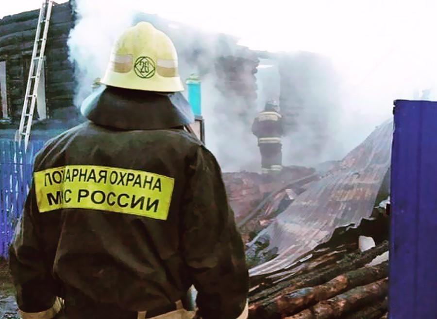 Пожарные работают на месте возгорания в деревянном доме