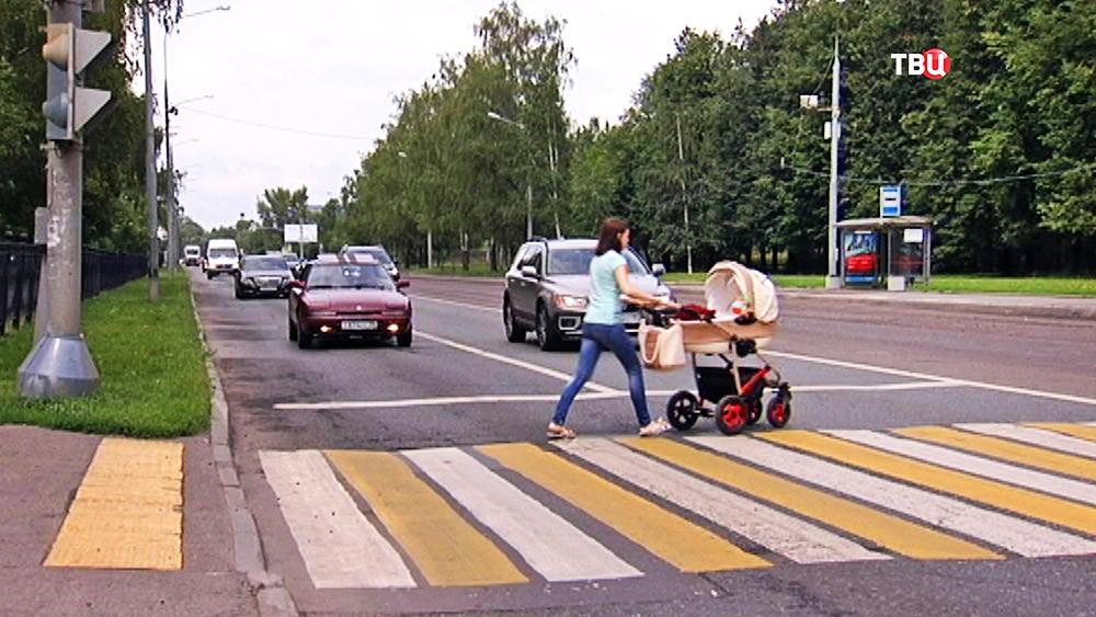 Женщина с коляской на пешеходном переходе