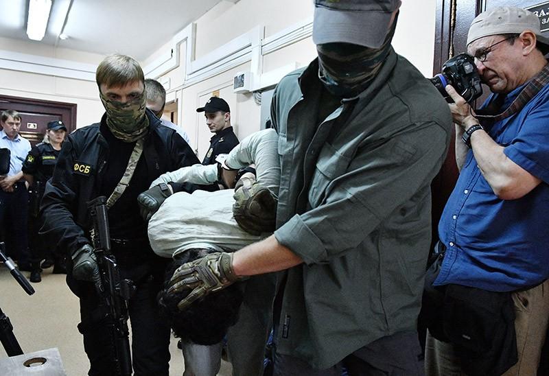 Сотрудники правоохранительных органов ведут одного из подозреваемых в подготовке взрывов в Москве