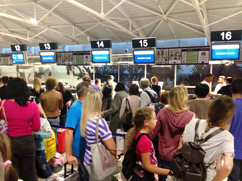 Пассажиры у стойки регистрации в аэропорте