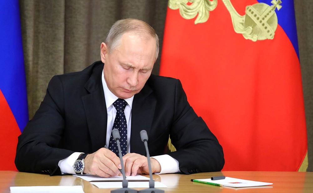 Президент России Владимир Путин подписывает закон