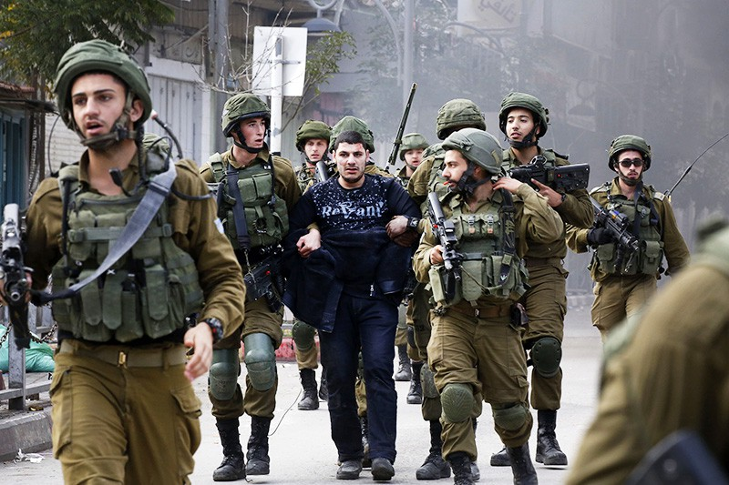 Израильские военные задерживают палестинского протестующего в ходе столкновений в Иерусалиме