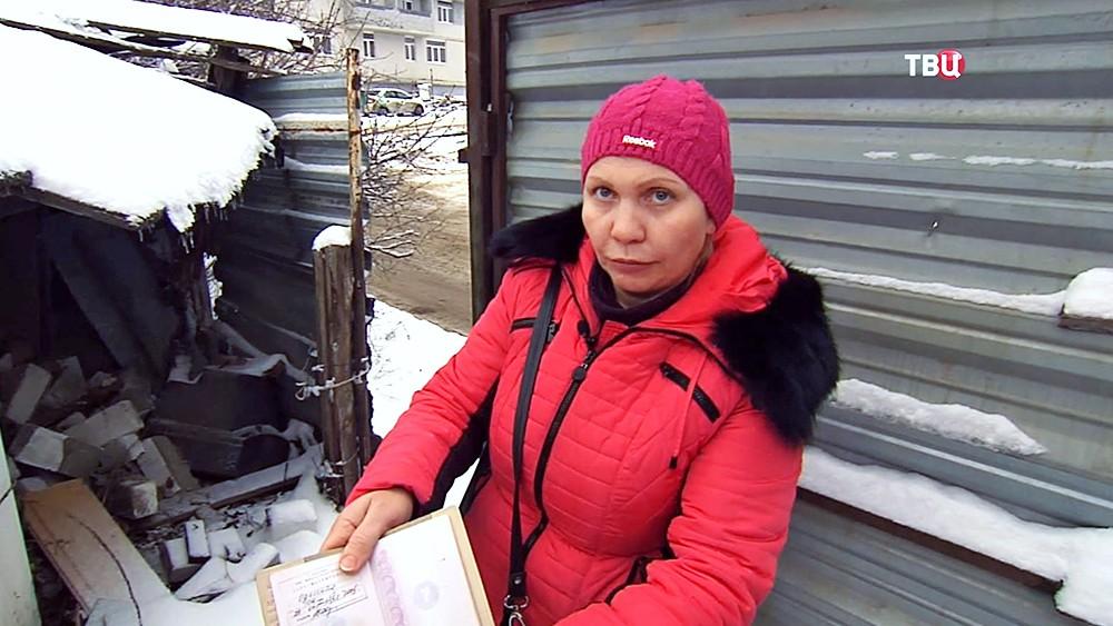Женщина показывает прописку в снесенном доме