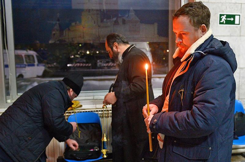 """Мужчина ставит свечу в аэропорту Орска в память о пассажирах, погибших в результате крушения самолета Ан-148 """"Саратовских авиалиний"""""""
