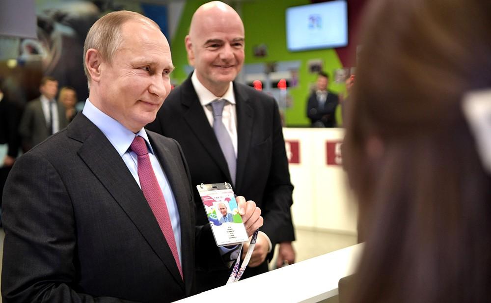 Владимир Путин и Джанни Инфантино получают паспорт болельщика