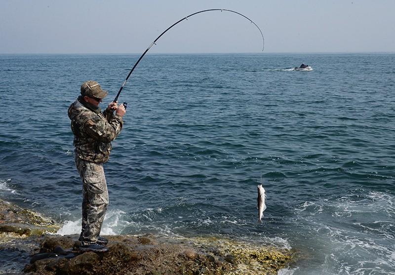 Рыбак ловит минтай