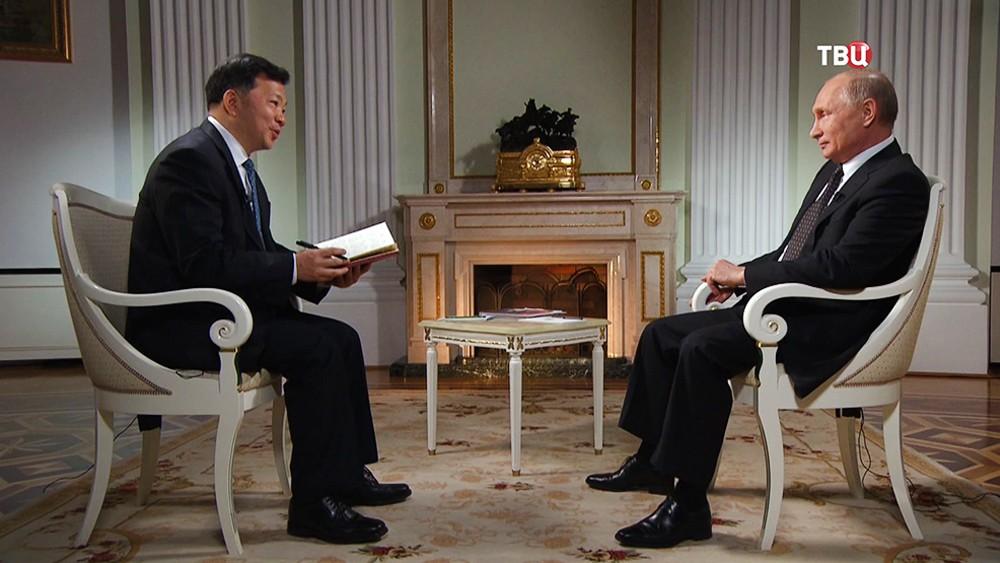Президент России Владимир Путин и председатель Медиакорпорации Китая Шэнь Хайсюн во время интервью