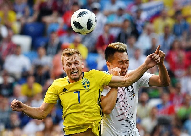 Себастьян Ларссон (Швеция) Ким Син Ук (Южная Корея) и в матче группового этапа чемпионата мира по футболу