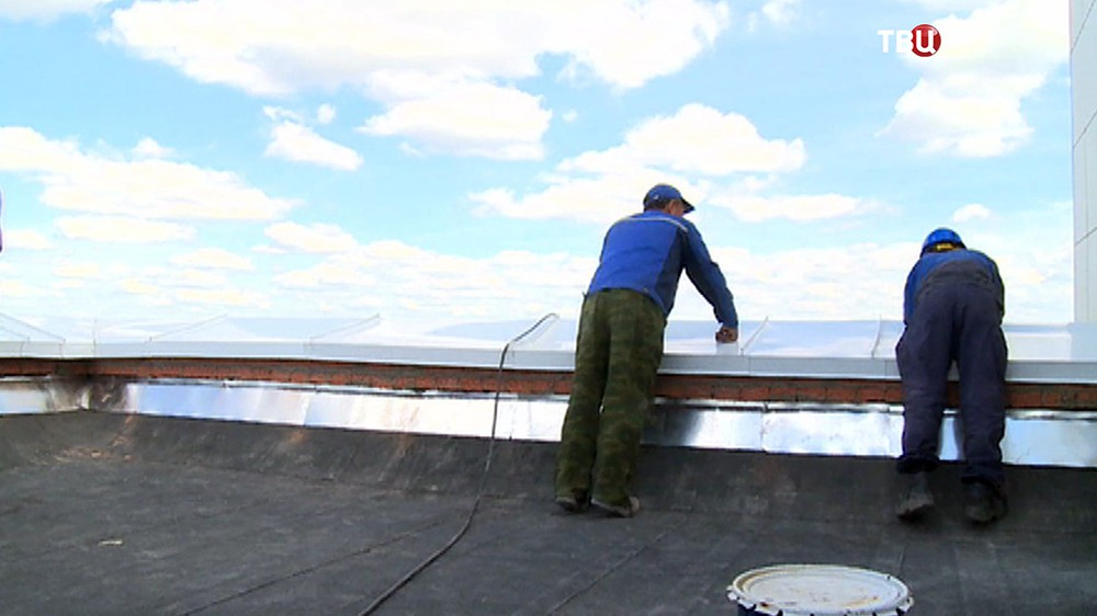 Строители на крыше дома