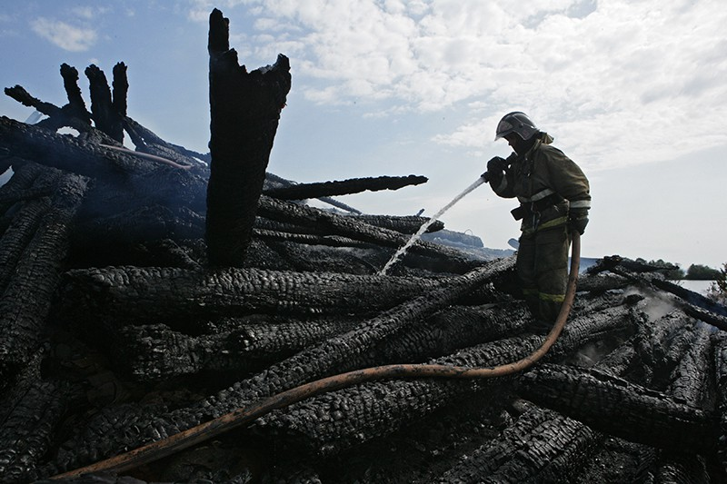 Сотрудник противопожарной службы у сгоревшего здания церкви Успения Божией Матери в Кондопоге в Карелии