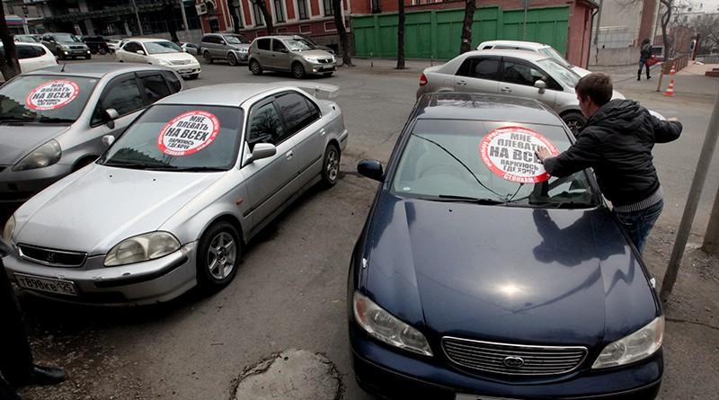"""Активист движения """"СтопХам"""" приклеивает наклейку на лобовое стекло автомобиля"""
