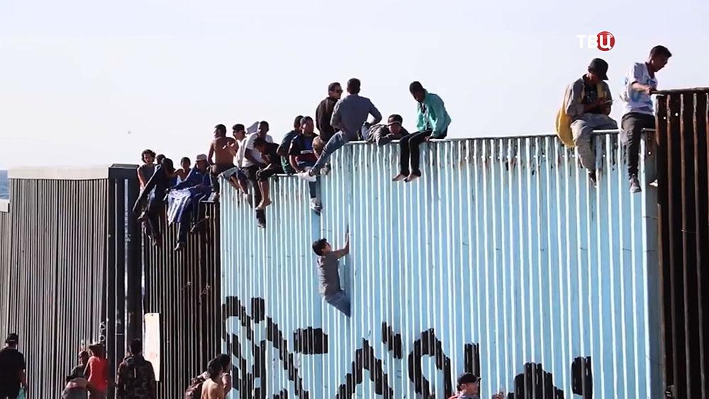 Мигранты на стене между Мексикой и США