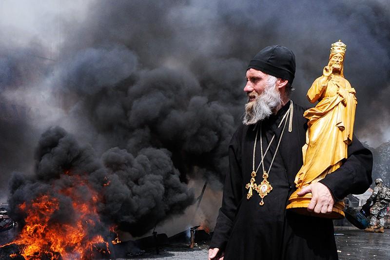 Священник во время беспорядков на Майдане Незалежности в Киеве