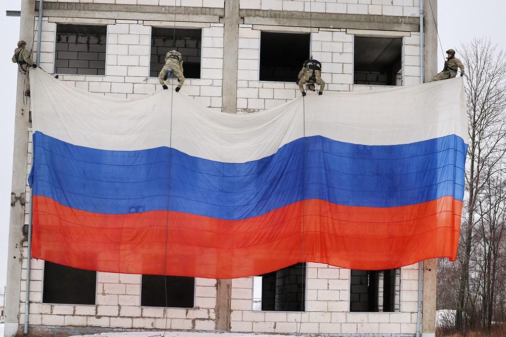 Бойцы росгвардии развернули на учебном здании десятиметровый российский триколор