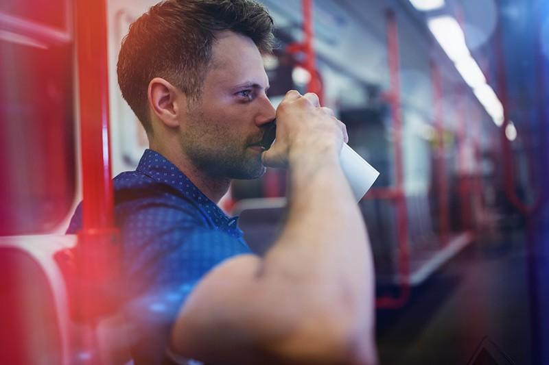 Пассажир пьет кофе в метро