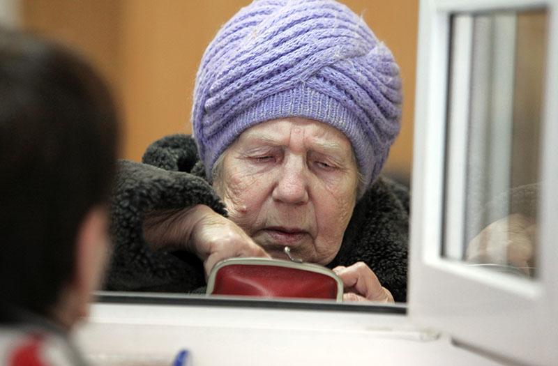 Женщина оплачивает коммунальные услуги в расчетно-кассовом центре