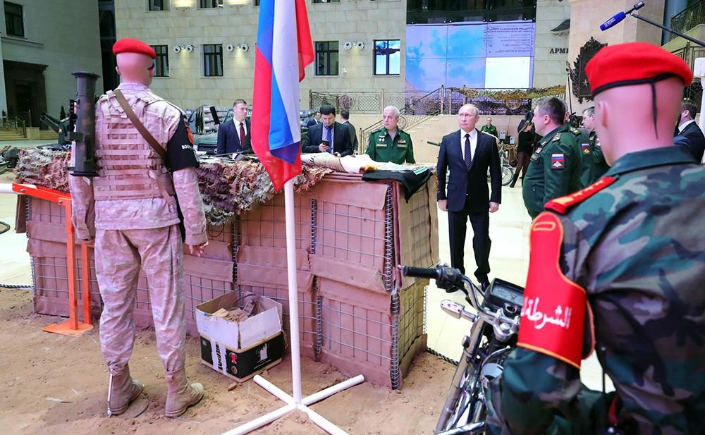 Владимир Путину осматривает изъятое у террористов в Сирии оружие