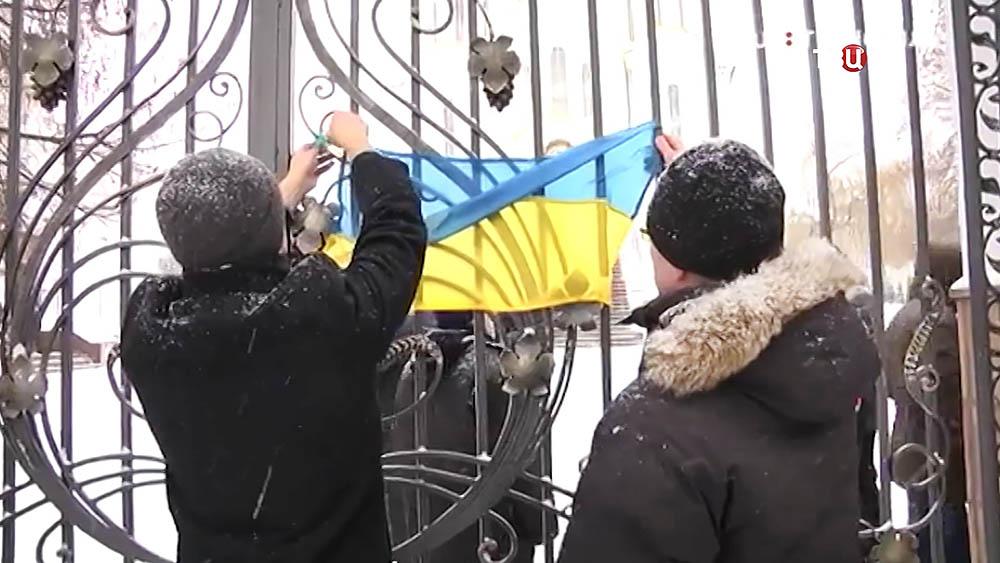 Украинские радикалы несут вешают на ограду храма флаг