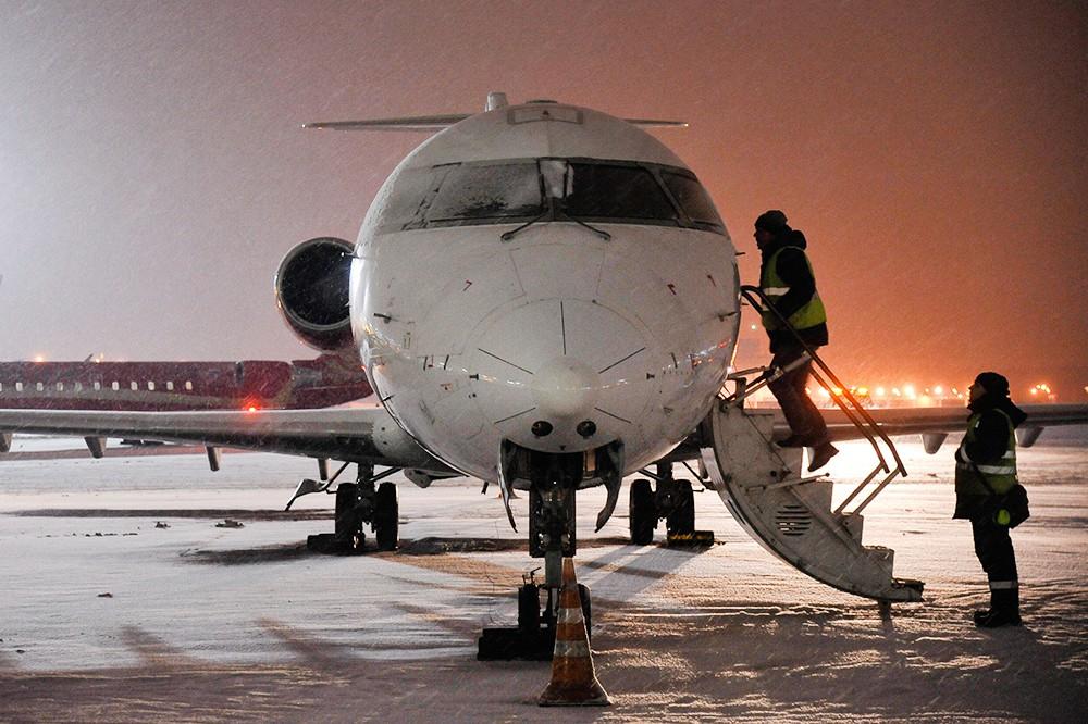 Служащие аэропорта осматривают самолет