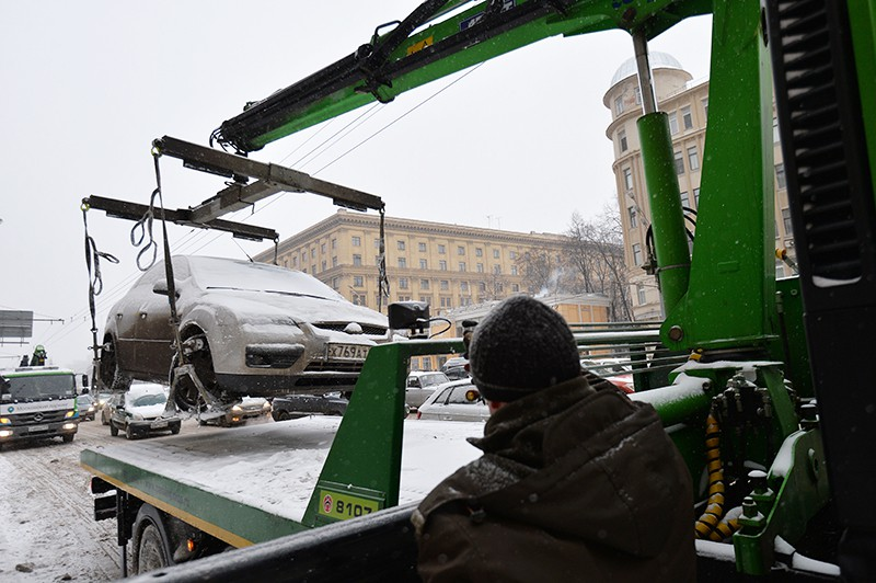 Сотрудник дорожной службы во время эвакуации неправильно припаркованного автомобиля