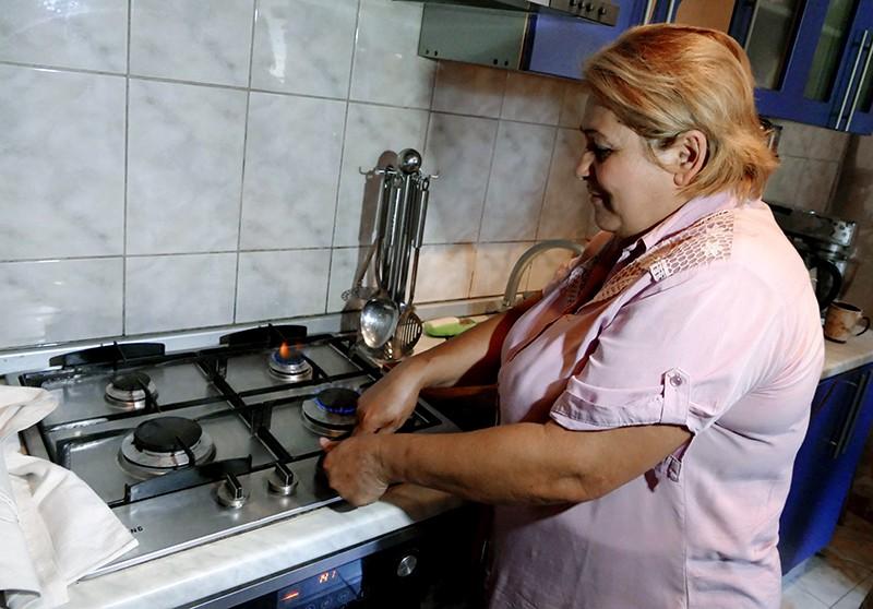 Женщина включает газовую плиту