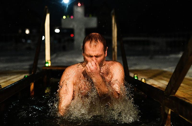 Мужчина во время традиционных купаний в праздник Крещения