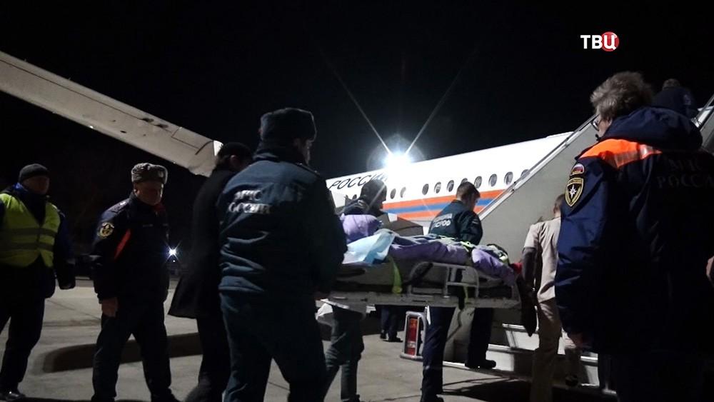 Сотрудники МЧС заносят пострадавшего на спецборт