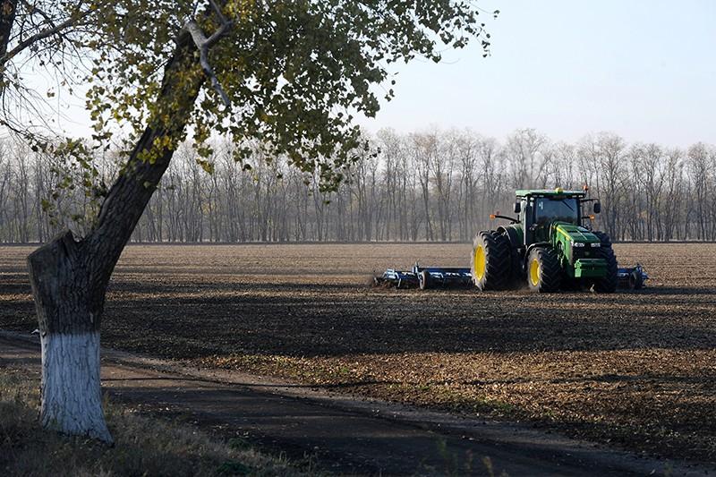 Трактор боронит вспаханное поле