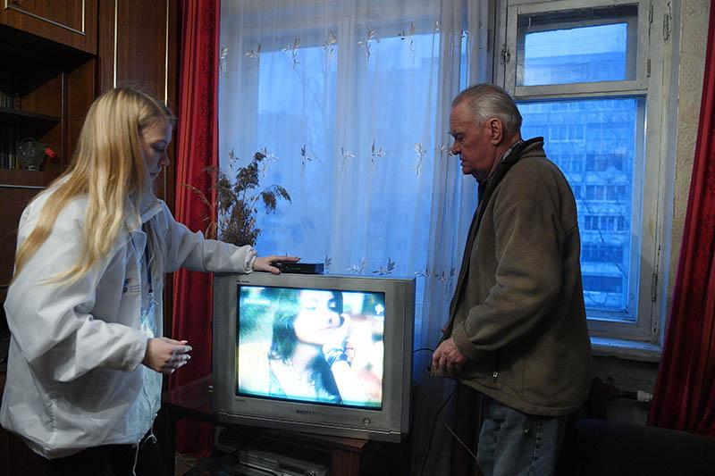 Девушка-волонтер помогает настроить работу телевизора с приставкой для цифрового вещания