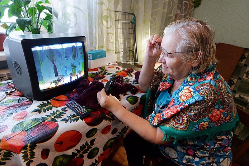 Пожилая женщина смотрит телевизор