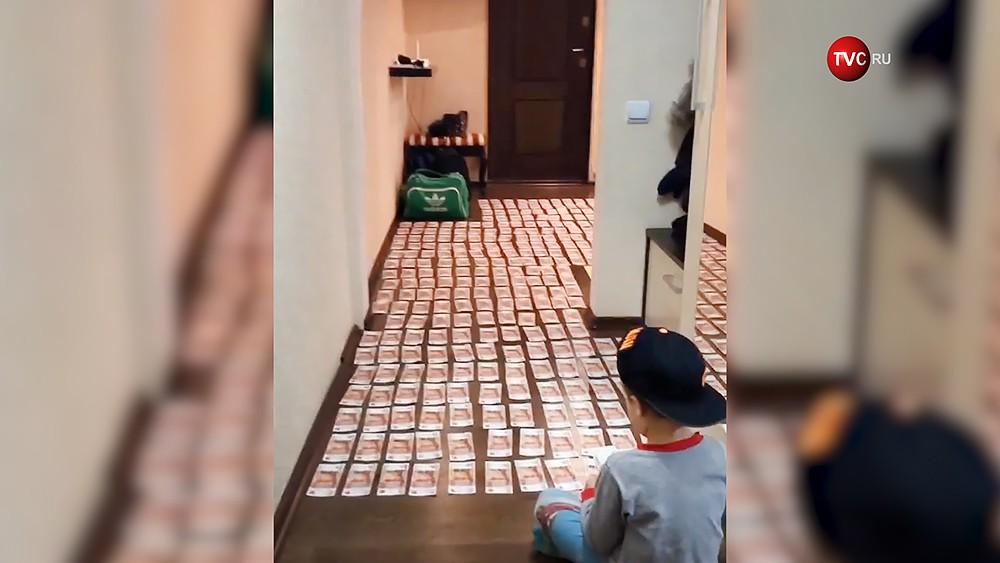 Дети выложили ковер из денег