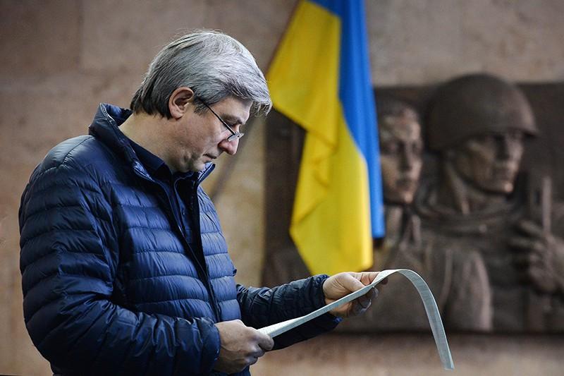 Мужчина с бюллетенями во время голосования на Украине