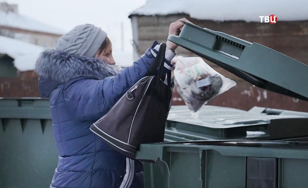 Женщина вбрасывает мусор