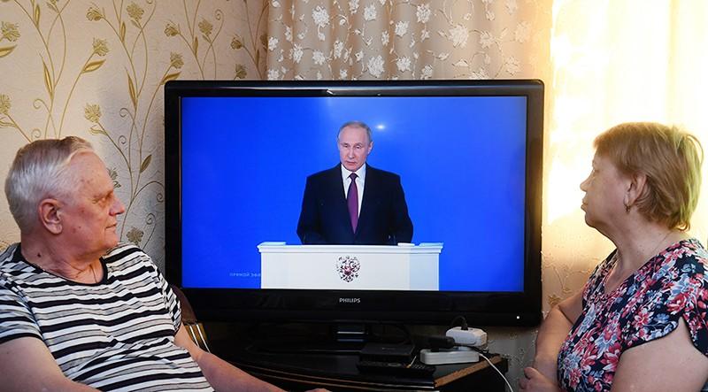 Мужчина и женщина смотрят трансляцию ежегодного послания президента РФ Владимира Путина к Федеральному собранию